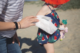A parent wiping a toddler's arm with a WaterWipes Nose To Toes XL Bathing Wipe