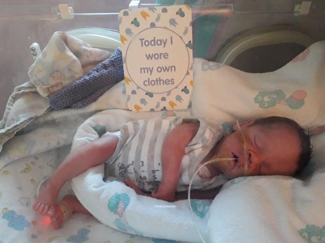 Preemie baby with milestone card