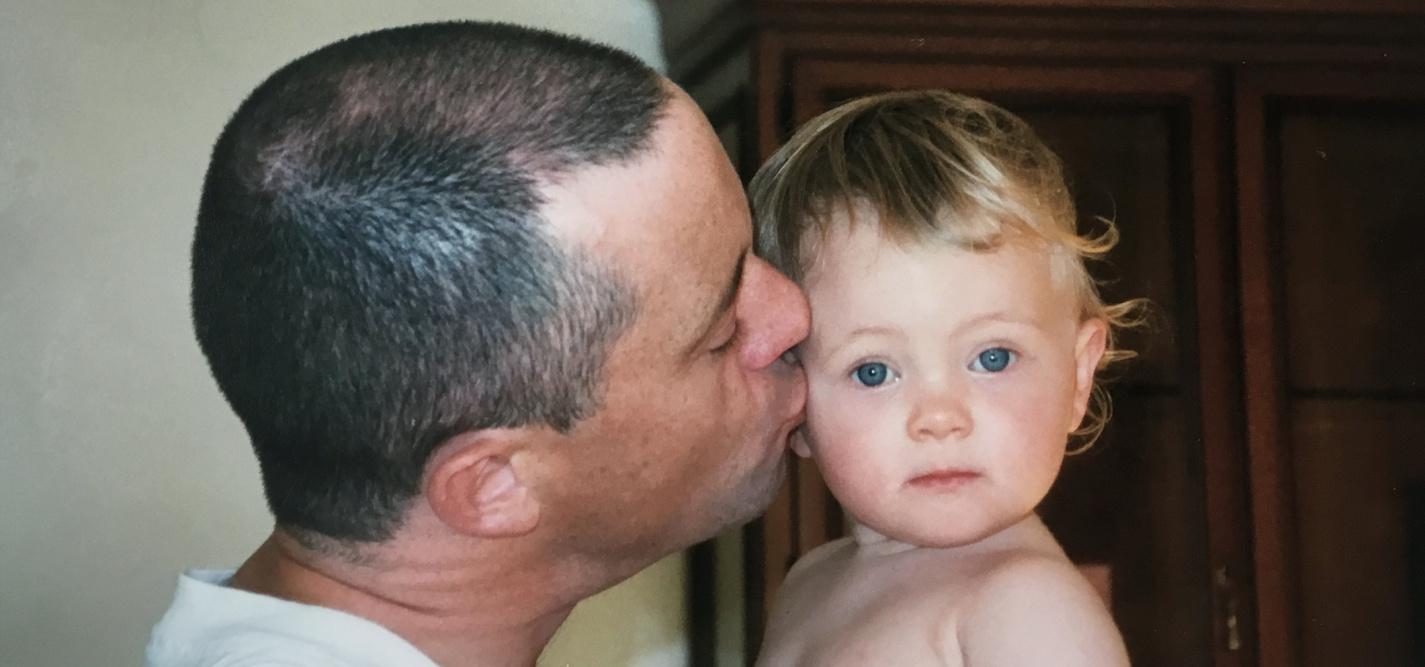 Pai a beijar o seu bebé, expressando afeto e cuidado.