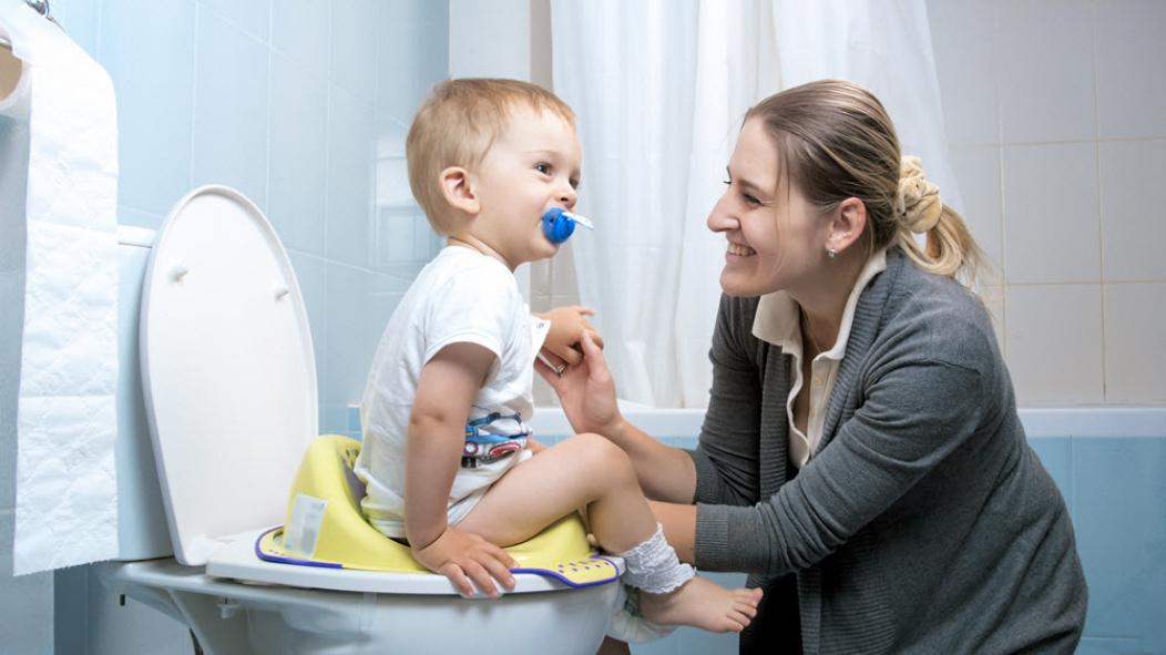 Niño en el inodoro con su madre.