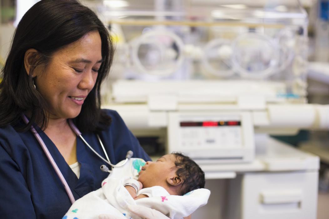 nurse holding baby in NICU