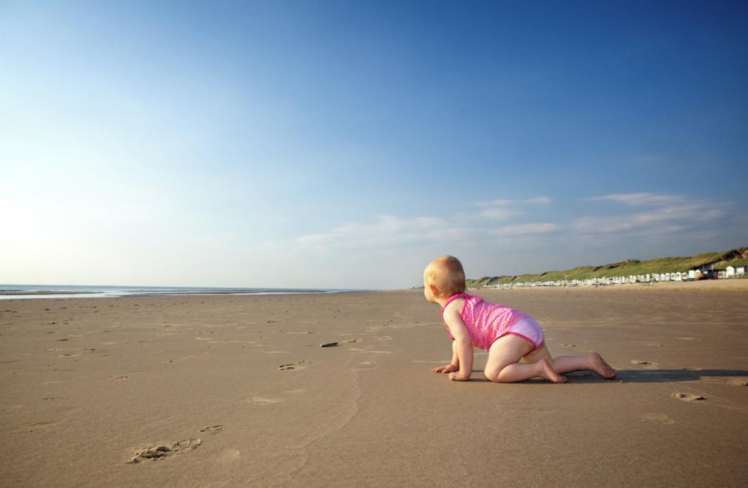 Un bébé qui rampe sur une plage de sable