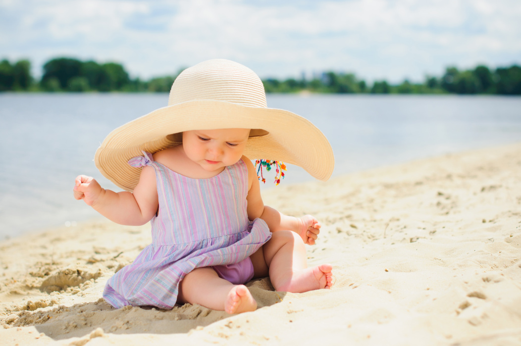 baby girl playing on sand